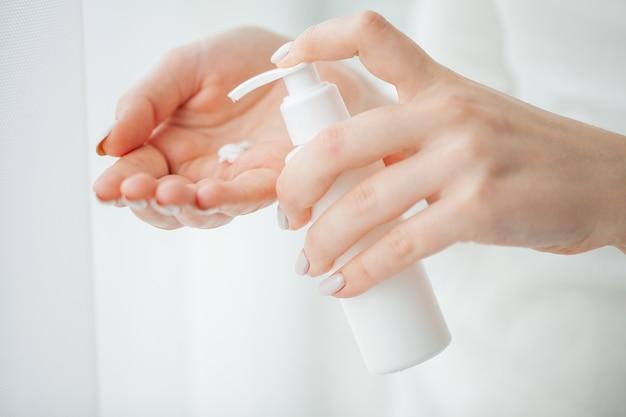 Cuidado de la piel. manos de mujer hermosa con crema.