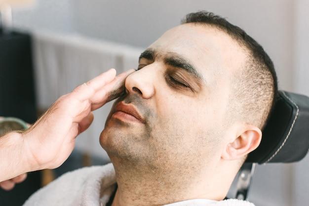 Cuidado de la piel masculina en un salón de belleza. aplicando mascarilla limpiadora de arcilla en la cara de un hombre