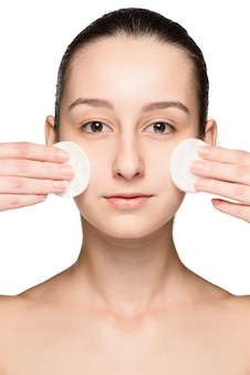 Cuidado de la piel mujer quitando la cara con hisopos de algodón