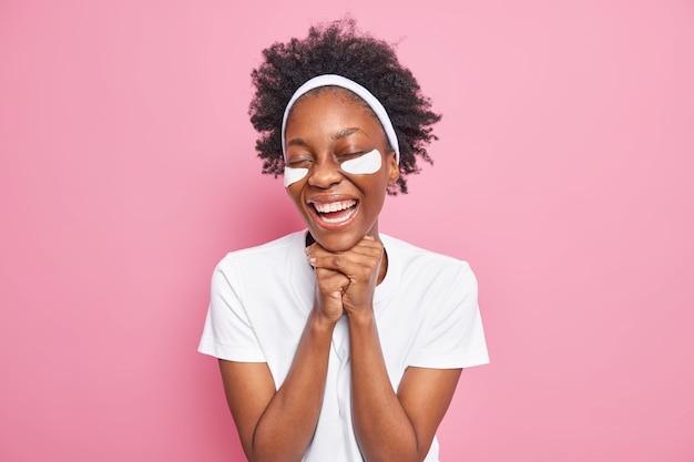 Cuidado de la piel de los ojos. alegre joven afroamericana mantiene las manos debajo de la barbilla sonríe aplica ampliamente parches de colágeno para eliminar las líneas finas