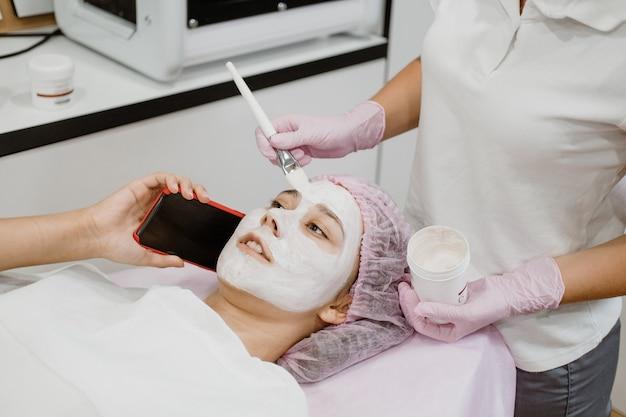 Cuidado de la piel profesional en salón de belleza. mujer joven con mascarilla de arcilla toma selfie en teléfono
