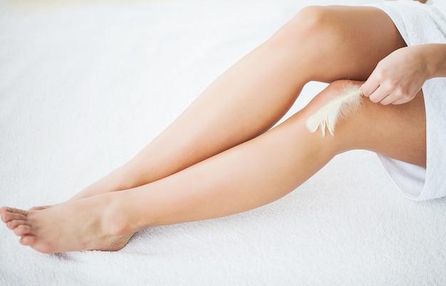 Cuidado de la piel y salud. depilación. mujer con pluma tocando las piernas desnudas en la cama