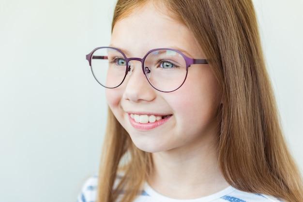 Cuidado de la salud, control del globo ocular, concepto de visión clara. close up retrato de colegiala sonriente en gafas rojas y púrpuras
