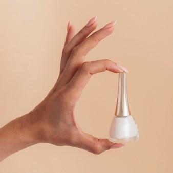 Cuidado saludable de manicura sosteniendo un esmalte de uñas