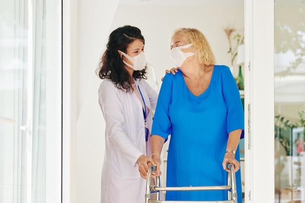 Cuidador ayudando a mujer mayor