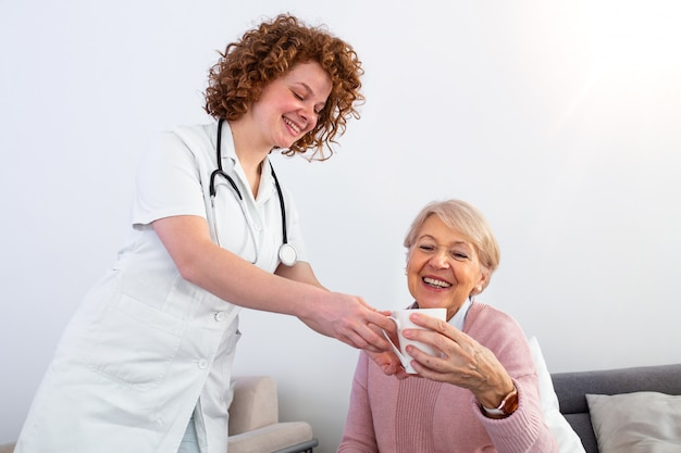 Cuidador bastante joven que sirve la taza de té de la tarde a una mujer mayor feliz. joven enfermera cuidando a un paciente anciano en su casa.