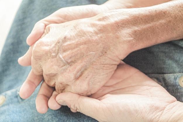 Cuidador, cuidador mano sosteniendo la mano mayor en cuidados paliativos