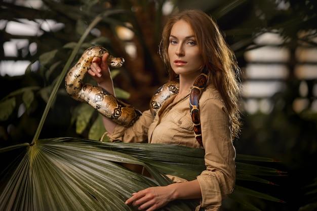 Cuidador femenino atractivo con serpiente pitón en la naturaleza tropical