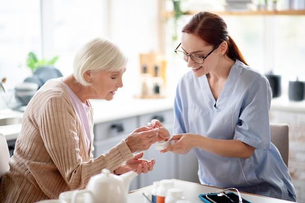 Cuidador con gafas que le dan vitaminas a una anciana