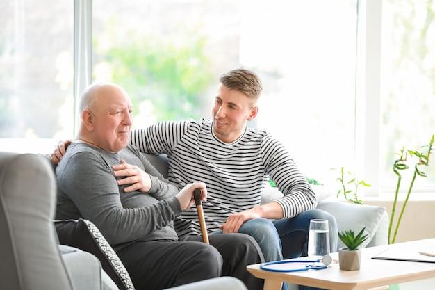 Cuidador masculino con hombre mayor en hogar de ancianos