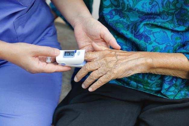 Cuidador monitoreando la saturación de oxígeno en la punta del dedo de una anciana