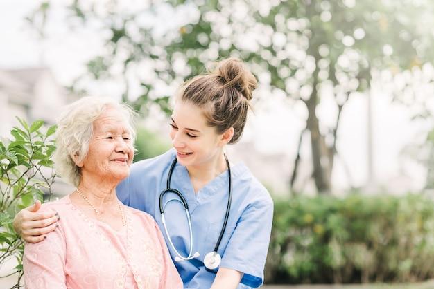 Cuidador con mujer anciana asiática al aire libre