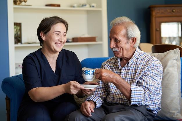 Cuidador profesional y útil y un hombre mayor durante la visita al hogar