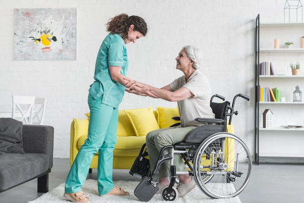 Cuidador que ayuda al paciente femenino mayor que se sienta en la silla de rueda