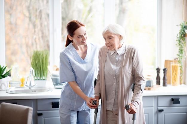 Cuidador sonriente ayudando a anciana a hacer pasos