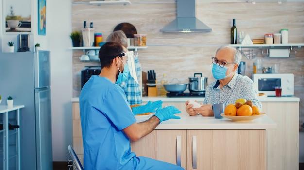 Cuidador sosteniendo una botella de píldoras para un paciente mayor durante la visita domiciliaria pandémica de coronavirus con mascarilla facial enfermero trabajador social en pareja de ancianos jubilados explicando la propagación del covid-19