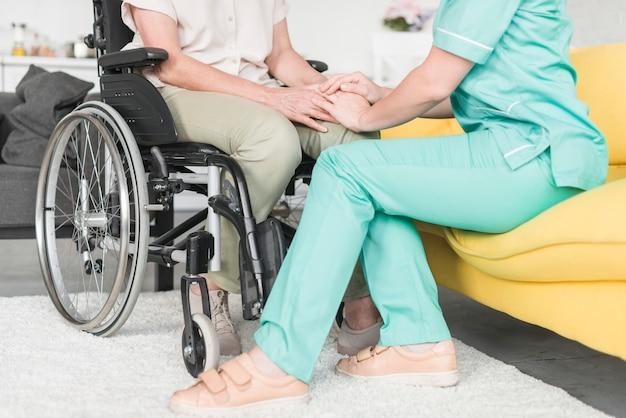 Cuidador, tenencia, mano, de, paciente femenino, sentado, en, silla de ruedas