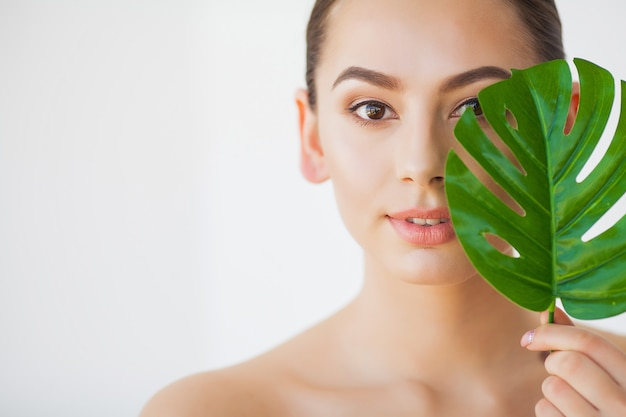 Cuidados del spa. joven mujer bonita morena con gran hoja verde