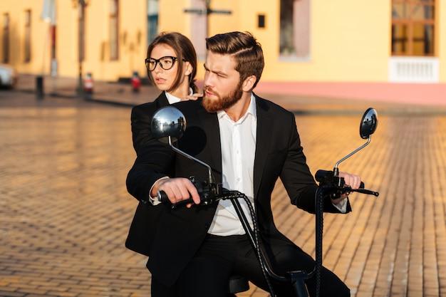 Cuidadosa pareja de negocios monta en moto moderna en el parque