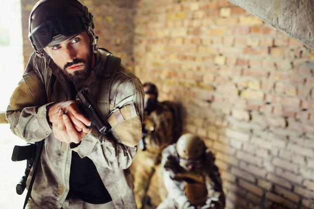 Cuidadoso soldado está de pie con sus combates en una habitación.