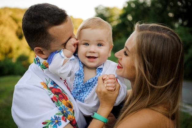 Cuidadosos padres sosteniendo en las manos a un bebé sonriente vestido con la camisa bordada