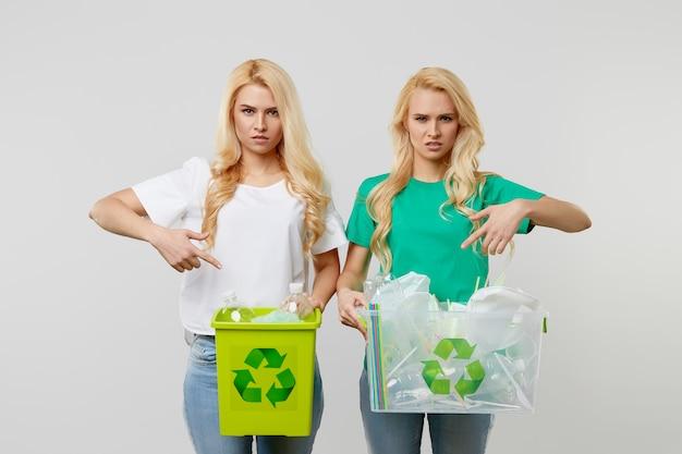 Cuidando la naturaleza. las mujeres jóvenes con una camiseta verde sostienen una caja con botellas de plástico y desechos. los voluntarios compilaron basura y la llevaron al reciclaje.