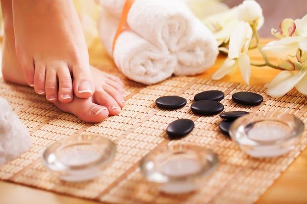 Cuidar las piernas de una mujer hermosa en el suelo.