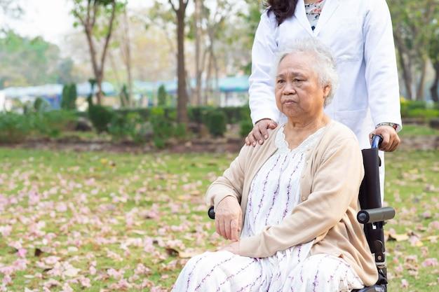 Cuide la ayuda y cuide al paciente asiático mayor de la mujer que se sienta en la silla de ruedas en el parque.