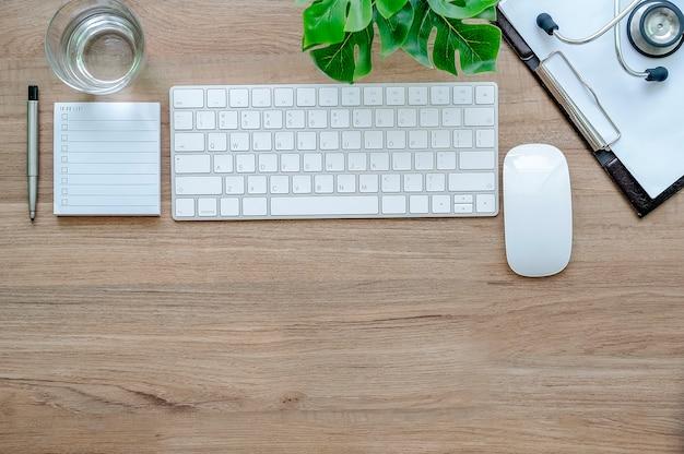 Cuide el concepto de trabajo del escritorio, el teclado blanco, el ratón, la carta y el estetoscopio en la tabla de madera.
