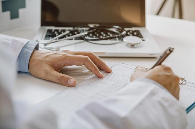 Cuide llenar el formulario médico mientras que se sienta en el escritorio en oficina del hospital. médico en el trabajo.