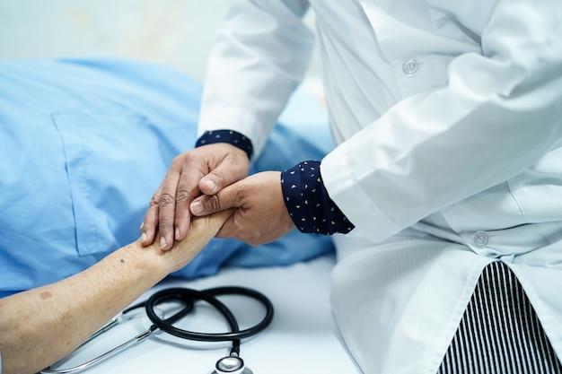 Cuide las manos conmovedoras mayores o mayores asiáticas del paciente de la tenencia de la mujer del paciente con amor, cuidado.