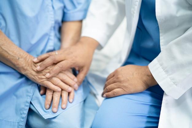 Cuide las manos conmovedoras paciente asiático mayor de la mujer con amor.