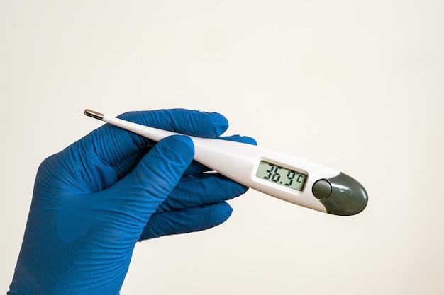 Cuide las manos en guantes protectores azules que sostienen el termómetro médico que muestra temperatura levemente alta.