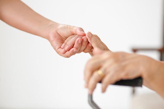 Cuide a una mujer asiática mayor que usa un bastón en casa con el cuidador