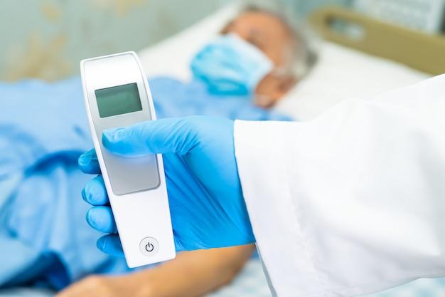 Cuide sostener el termómetro digital para medir al paciente asiático mayor de la mujer que lleva una mascarilla.