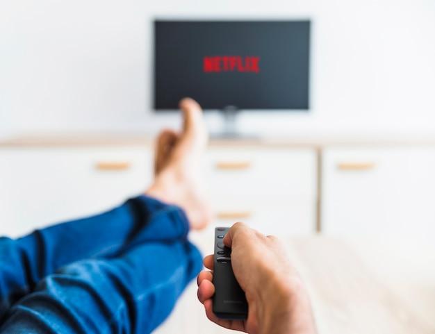 Cultivar a un hombre usando el control remoto mientras ve la serie netflix