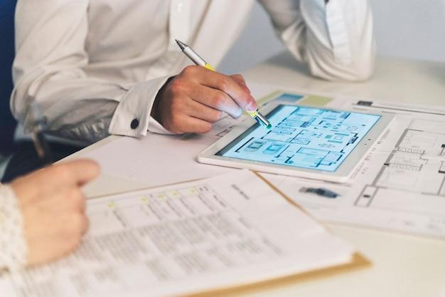 Cultivar personas que trabajan con planes en tableta