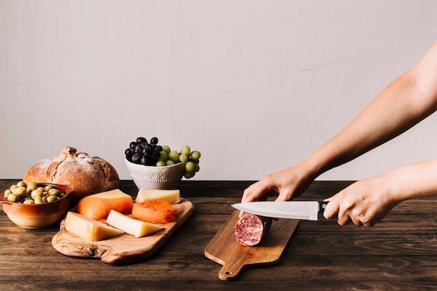 Cultive las manos cortando salchichas cerca de los alimentos