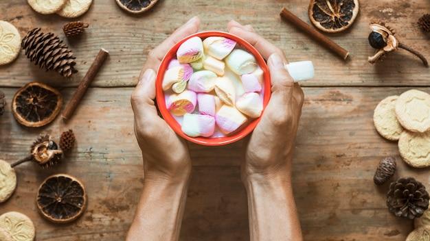 Cultive las manos con chocolate caliente cerca de las especias