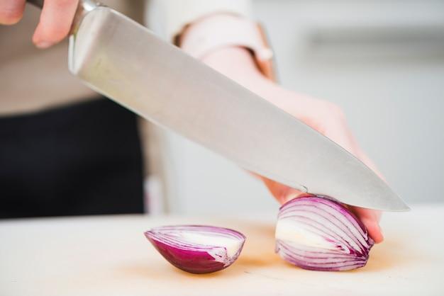 Cultive las manos cortando cebolla con cuchillo