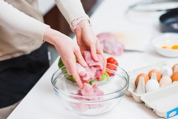 Cultive las manos poniendo la carne cruda en el plato