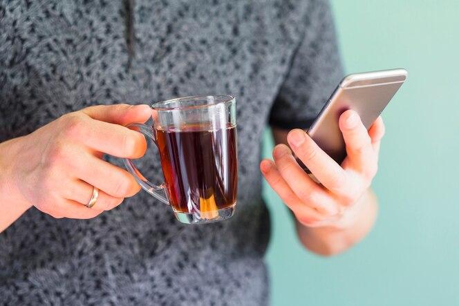Cultivo hombre sosteniendo bebida y teléfono inteligente