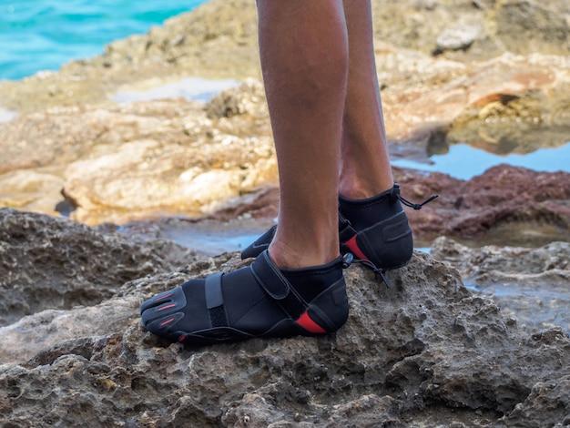 Cultivo un hombre con zapatos de arrecife está de pie sobre un arrecife. piedras afiladas cerca del oceano.