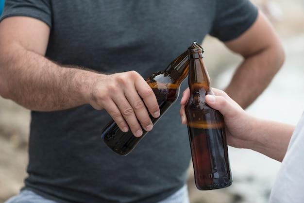 Cultivo hombres tintineo de botellas en la playa