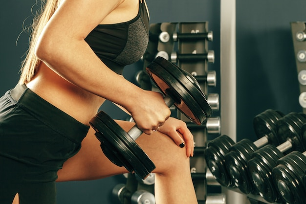 Cultivo de mujer vistiendo ropa deportiva haciendo ejercicio con pesas en el gimnasio