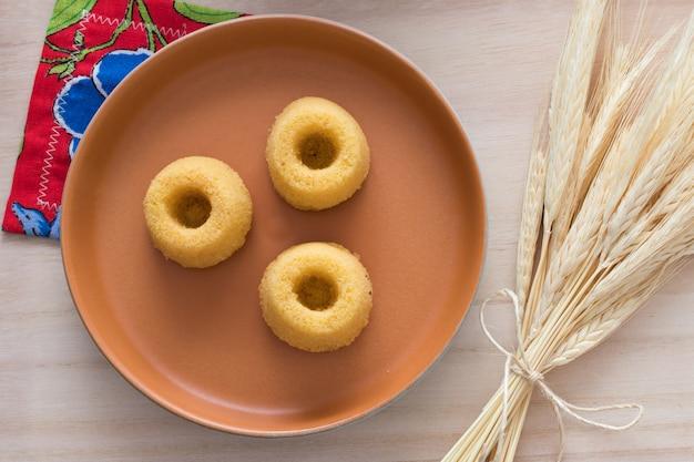 Cultura brasileña. mini pastel de harina de maíz en un hermoso plato rústico y trigo
