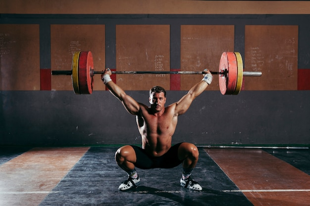 Culturismo en gimnasio con hombre fuerte