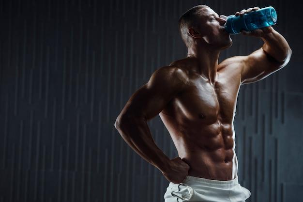 Culturista agua potable después del entrenamiento físico