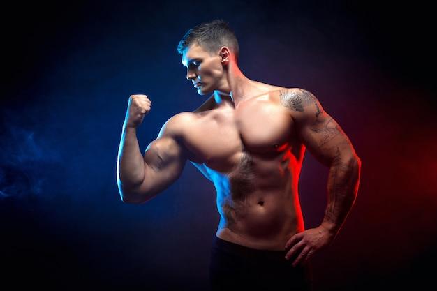 Culturista atlético guapo guapo. cuerpo musculoso fitness sobre fondo oscuro humo. hombre perfecto impresionante culturista, tatuaje, posando.
