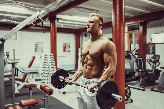 Culturista atlético muy poderoso, realiza ejercicio con pesas